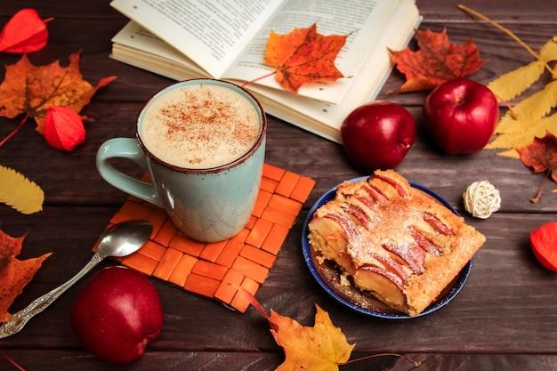 Torta de maçã, um livro, folhas amarelas, maçãs vermelhas e uma xícara de café em uma mesa de madeira escura