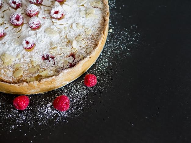 Torta de mascarpone com framboesas frescas, amêndoa e açúcar em pó em uma superfície preta
