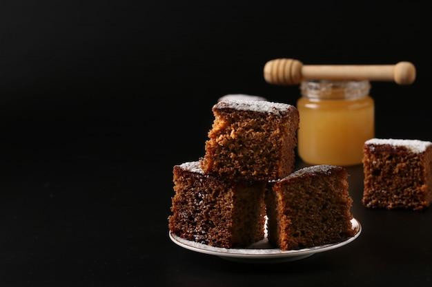 Torta de mel doce tradicional no feriado de ano novo judaico de rosh hashaná em um fundo escuro