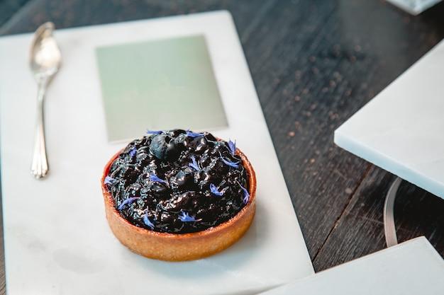 Torta de mirtilo em uma placa de mármore e colher de ouro em um restaurante com espaço de cópia.