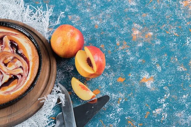 Torta de morango com pêssegos amarelos ao redor.