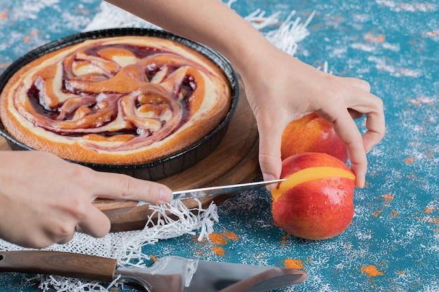 Torta de morango com pêssegos frescos ao redor.