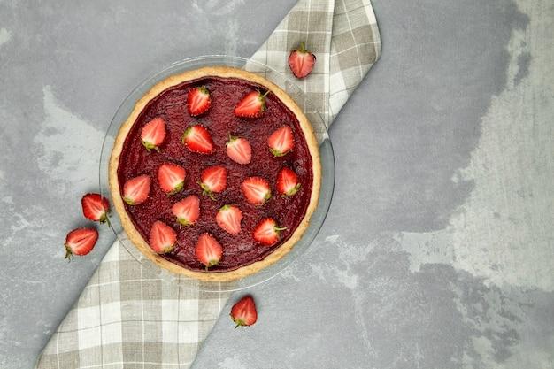 Torta de morango decorada com frutas frescas na mesa de concreto cinza, vista de cima, espaço de cópia