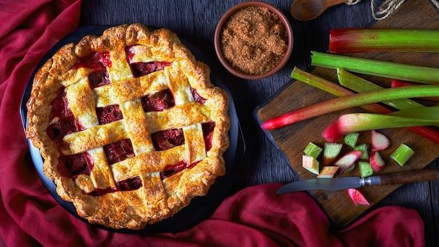 Torta de morango e ruibarbo caseira em uma mesa de madeira escura com ingredientes e um pano marrom-avermelhado, vista horizontal de cima, camada plana, close-up