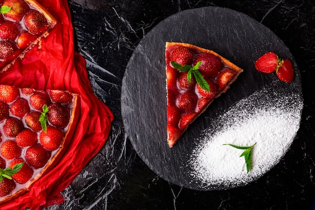 Torta de morango na placa de ardósia preta.