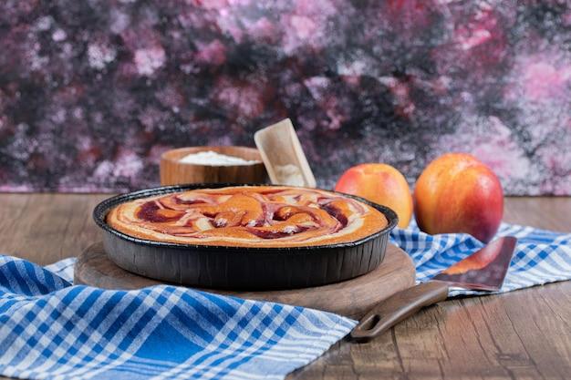 Torta de morango servida com pêssegos vermelhos e amarelos.