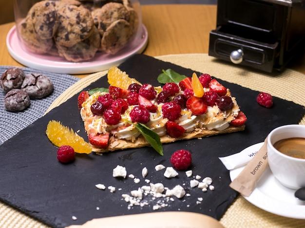 Torta de napoleão com creme de framboesa laranja cereja marshmallows hortelã vista lateral