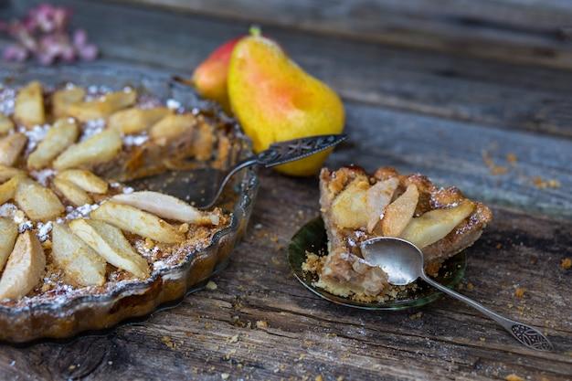 Torta de peras, uma fatia de torta em um prato e peras