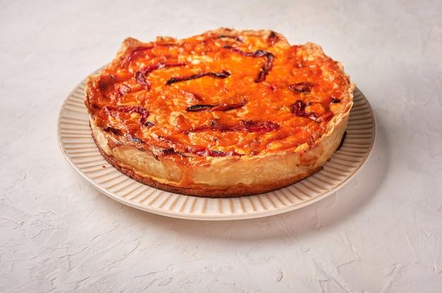 Torta de quiche caseira com frango, tomate seco e queijo cheddar em superfície clara close up