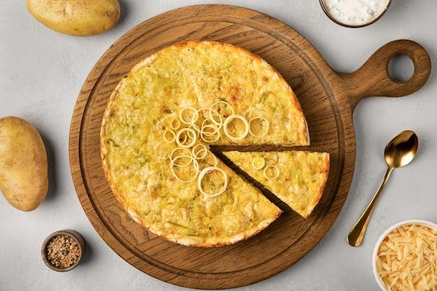 Torta de quiche com batata alho-poró e queijo espalhada sobre fundo cinza de concreto e ingredientes