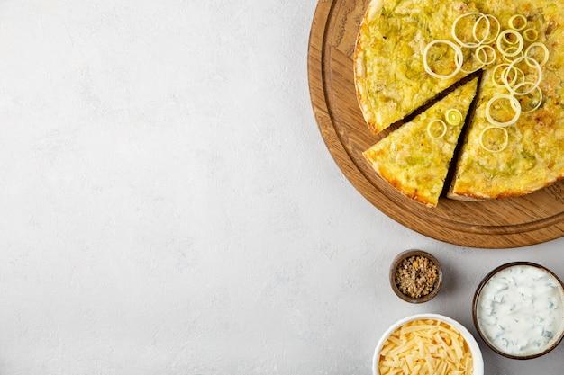 Torta de quiche com batata com alho-poró e queijo plano sobre fundo cinza de concreto com espaço de cópia