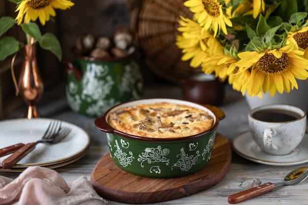 Torta de quiche com cogumelos em uma mesa de madeira.