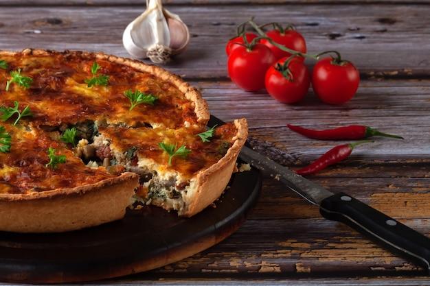 Torta de quiche tradicional francesa com frango e cogumelos em uma mesa de madeira