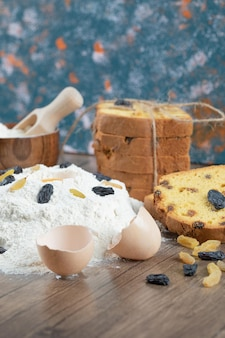 Torta de sultana com ingredientes no deck de madeira.
