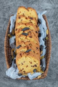 Torta de sultana fatiada em uma cesta de madeira sobre o pano de prato