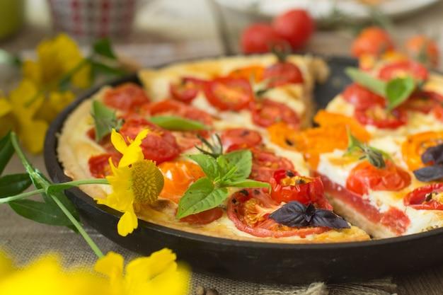 Torta de tomate feita com massa quebrada, tomate vermelho e amarelo, queijo e creme. conceito de alimentação saudável ou comida vegetariana em fundo de madeira rústica
