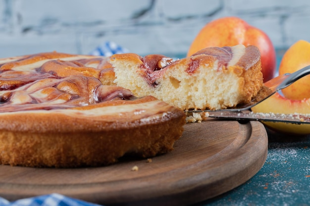 Torta de xarope de morango com pêssegos amarelos ao redor.