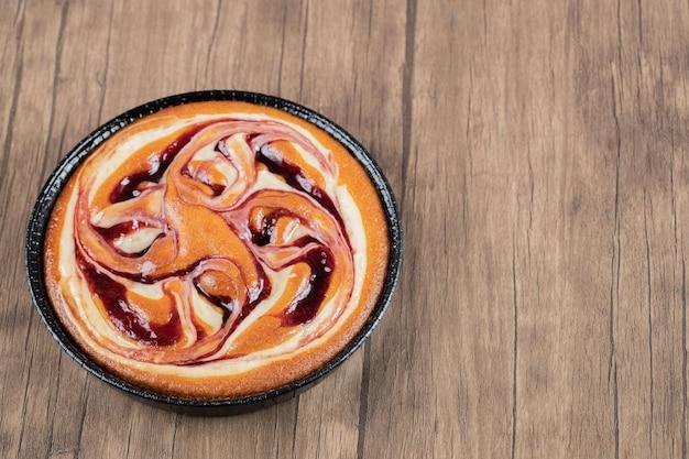 Torta de xarope de morango na forma metálica preta.