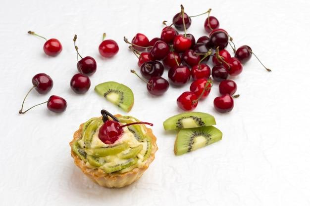 Torta decorada com cereja vermelha e kiwi. kiwi e cereja vermelha na superfície branca. vista do topo. copie o espaço.