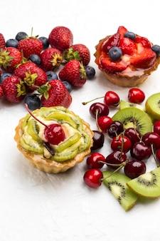 Torta decorada com frutas frescas. morango e mirtilos, kiwi e cereja vermelha na superfície branca. espaço da cópia plana lay.