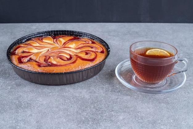 Torta deliciosa com frutas vermelhas e xícara de chá na superfície de mármore