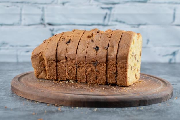 Torta doce de baunilha com ingredientes em travessa de madeira rústica