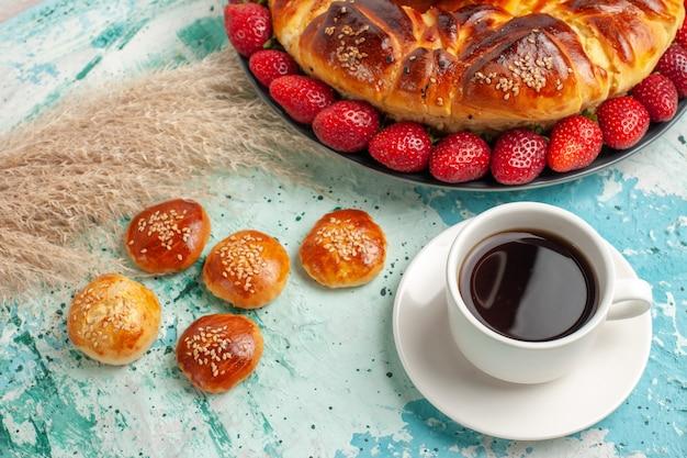 Torta doce gostosa de vista frontal com morangos vermelhos frescos e bolinhos na superfície azul