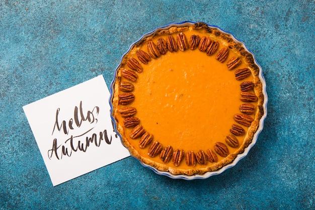 Torta e fatia de abóbora com porca de noz-pecã e canela no fundo concreto azul, vista superior, espaço da cópia. pastelaria caseira de outono para o dia de ação de graças