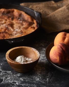 Torta e uma tigela de pêssegos em uma superfície preta coberta com farinha