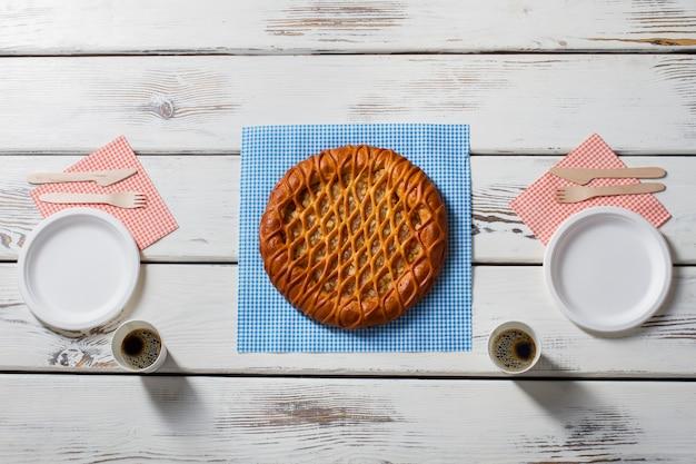 Torta em guardanapo e talheres. copos com bebida ao lado da torta. café da manhã saudável com café. almoço para casal.