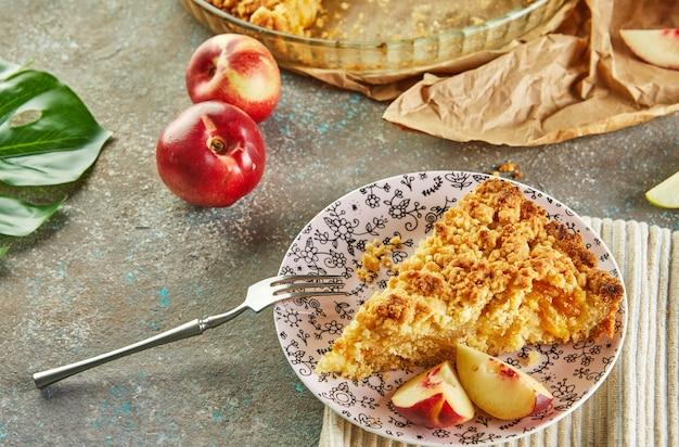 Torta em uma assadeira e uma fatia em um prato com pêssegos e peras