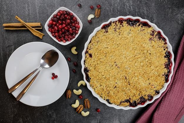 Torta esfarelada com cranberries e lingonberries em um fundo escuro com frutas, nozes e paus de canela