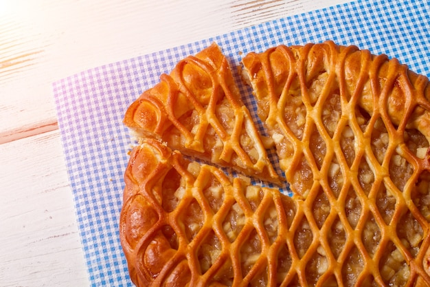Torta fatiada deitado no guardanapo. torta em fundo branco de madeira. deliciosa massa com recheio de frutas. saborosa refeição orgânica.