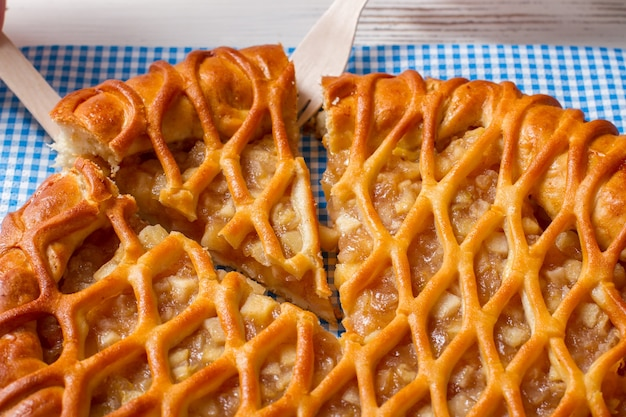 Torta fatiada e um garfo. talheres com pedaço de torta. produto fresco assado no café. pastelaria com maças e canela.