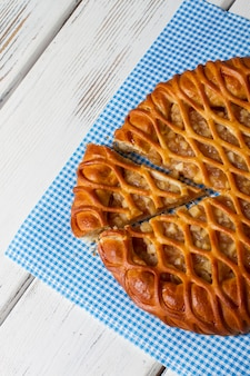 Torta fatiada em um guardanapo. produto cozido em fundo de madeira. nova receita de pastelaria tradicional. recheio de maçã suculento.