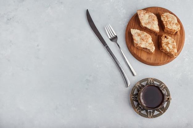 Torta fatiada em uma travessa de madeira com um copo de chá, vista de cima.