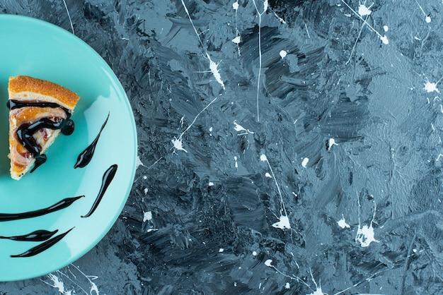 Torta fatiada no prato, na mesa azul.