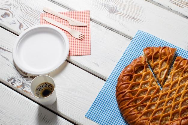Torta fatiada, prato e talheres. copo com bebida ao lado da torta. café da manhã simples servido no café. energia e frescor.