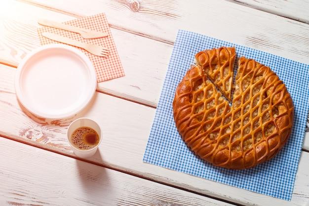 Torta fatiada, talheres e bebida. copo e prato ao lado da torta. carregue-se de energia. menu da manhã no bistrô local.