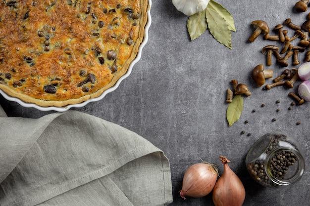 Torta francesa tradicional quiche lorraine com cogumelos, batata, queijo, cebola e temperos em um fundo escuro de concreto.
