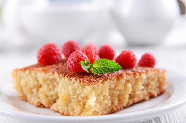 Torta fresca com framboesa em chapa branca na mesa de madeira closeup