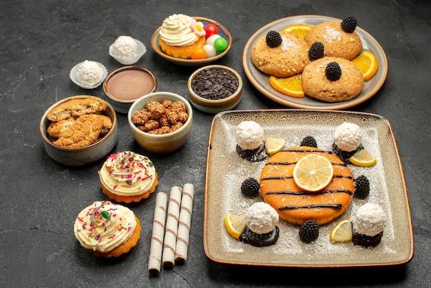 Torta gostosa de frente com biscoitos e bolo no fundo cinza bolo chá biscoito biscoito doce