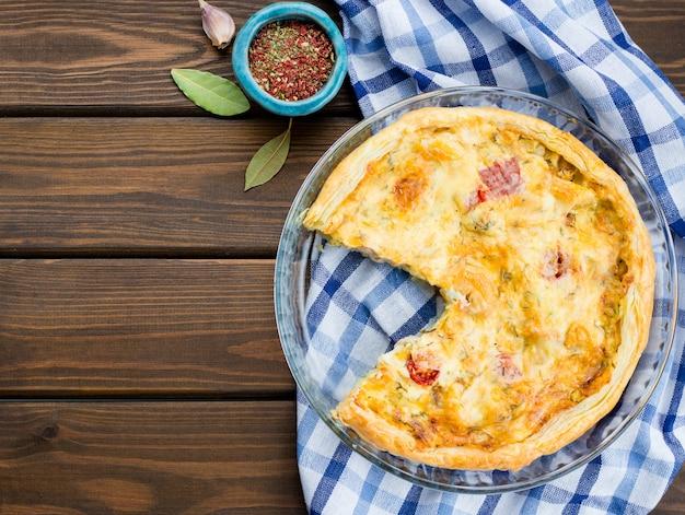 Torta grande rústica com pano sobre uma mesa de madeira, vista de cima, close-up