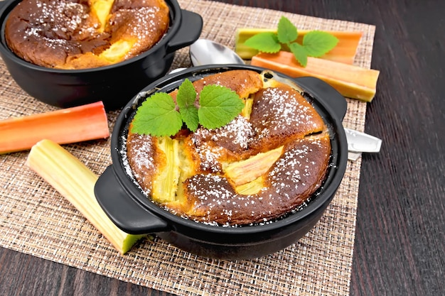 Torta klafouti com ruibarbo no braseiro preto, hastes de hortelã e ruibarbo em guardanapo de vime no fundo da prancha de madeira