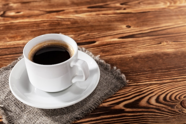 Torta na cama com a xícara de café em um fundo de uma mesa de madeira