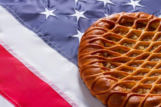 Torta no fundo da bandeira dos eua. produto cozido e bandeira brilhante. sobremesa tradicional com recheio de maçã. frescura e calor.