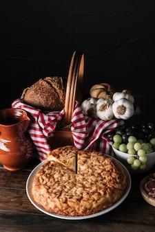 Torta perto de jarro e cesta com comida