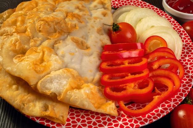 Torta picante com carne de cheburek com tomate, pimentão e ketchup encontra-se em um prato plano.