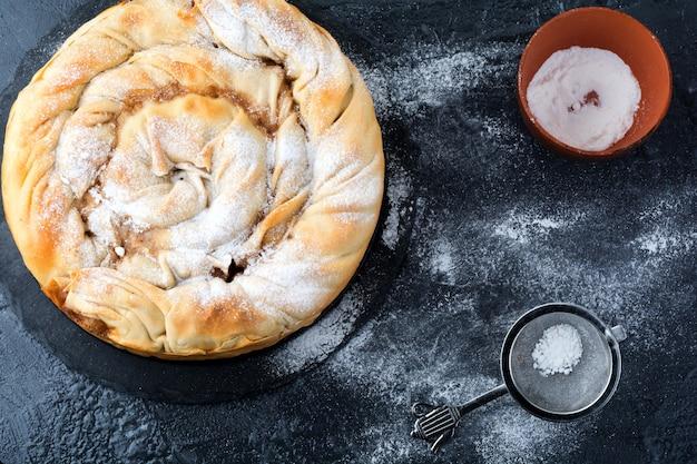 Torta redonda de burek com uma maçã em um fundo escuro. cozinha tradicional sérvia. foco seletivo. vista do topo.