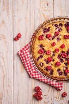 Torta saborosa com gelatina e frutas frescas de framboesa em assadeira com toalha de mesa vermelha